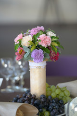 Wedding floral arrangement centerpiece with pastel colored carnations in a ivory vase decorated with pearly beads and with fresh white and red grapes positioned at its base