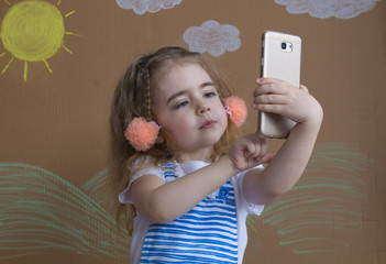 Close-up of a beautiful little girl smiling with a funny face makes selfie on a background in studio