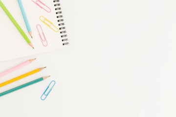 Flat lay photo of office desk with colorful pencil and paper clip,copy space top view