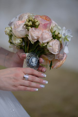 Cropped shot of young Caucasian bride with impeccable manicure holding a round pastel colored bouquet featuring a vintage cameo brooch with large white orchids, pink roses and berries
