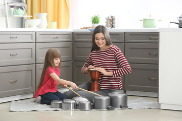 Mother and her daughter playing drums in kitchen