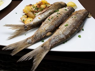 Three roasted sardines/ Roasted sardines in a restaurant in Wiesmar, North Germany
