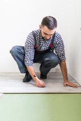 Male worker installing laminate flooring, man installing new wooden laminate flooring. Man laying laminate flooring at home. Carpenter worker installing laminate flooring in the room