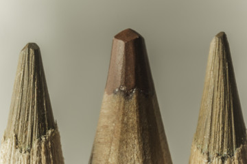 Macro photography of three brown pencils.Different shades.Manual and mechanical sharpening of pencils.Photo for the site about art,hobbies, education.