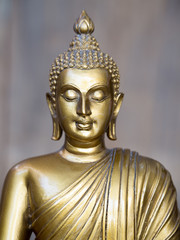 Golden antique buddha statue. The background is light slate gray. The face of the Buddha turned to the straight.