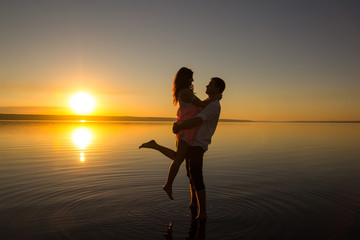 Young couple is embracing in the water on summer beach. Sunset over the sea.Two silhouettes against the sun. Just married couple hugging. Romantic love story. Man and woman in holiday honeymoon trip.