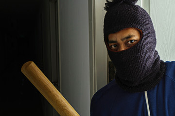 Masked robber with baseball bat hiding behind the door