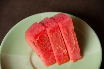 Slices of watermelon in a bowl, dark texture background