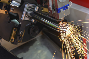 The fiber laser cutting machine cutting the steel pipe with the sparking light.
