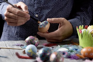 young man decorating homemade easter eggs