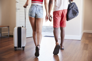 Detail Of Couple With Luggage Leaving Home For Vacation