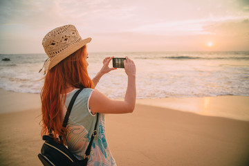 young woman tourist taking photo with smartphone on the beach at sunset
