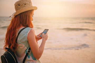 young woman tourist uses a smartphone on the ocean shore at sunset, rear view