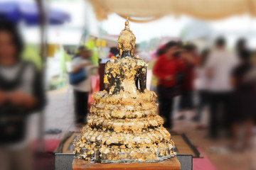 Buddha meditating on a lotus base 5 step. Gilded words surrounding . Photographed from behind
