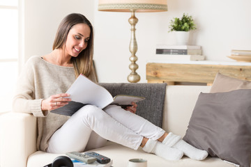 Smiling woman reading a magazine on a couch