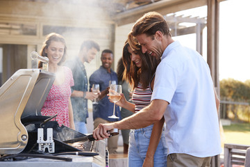 Group Of Friends Enjoying Barbecue At Home Together