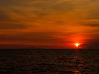 sunset last on horizontal in right frame over orange sky and ocean