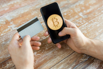 close up of bitcoin on smartphone and credit card