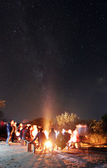 The people rest near a bonfire on the starry sky background. evening night time. long exposure