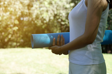 Close-up woman holding roll fitness or blue yoga mat after working out in the park. Healthy life concept