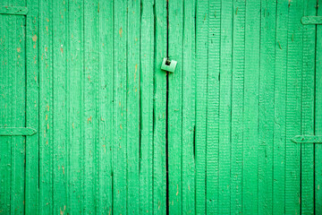 Green old wooden gate with a lock