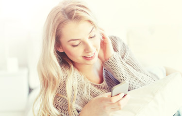 Fototapete - happy young woman with smartphone in bed at home