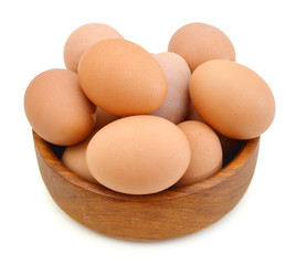 Raw eggs isolated in wooden bowl on white background