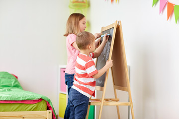 happy kids drawing on chalk board at home