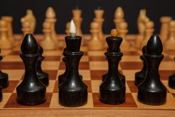 Black and white wooden chess pieces on board with black background