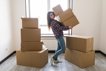 Young woman is transporting a filled cardboard in new apparment