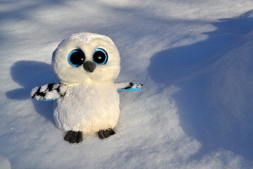 Cute owl toy on the snow outdoor.