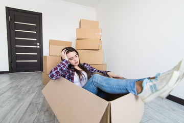 Cheerful sad and tired woman sitting in a cardboard box white moving in new appartmant