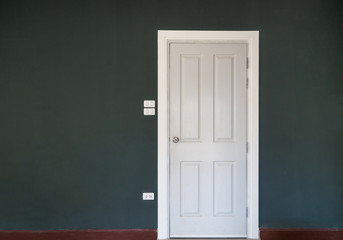 close white old wood door on dark gray wall