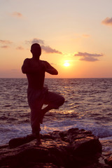 Man standing in yoga tree pose on ocean beach at sunset