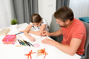 High angle portrait of bearded father helping little girl drawing handmade card for mothers day at home in modern living room