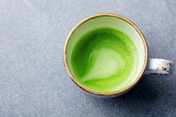 Matcha, green tea latte in a cup. Grey stone background. Top view. Close up.