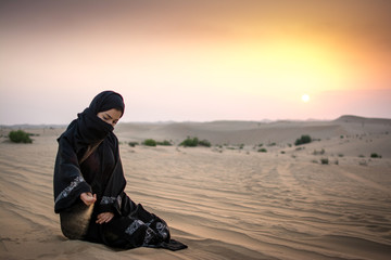 Beautiful young woman in hijab pouring sand while sitting on desert dune during sunset.