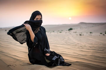 Portrait of Muslim woman sitting on sand in the desert during sunset. Beautiful young woman holding veil to cover her face.