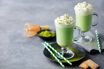 Matcha green tea latte with whipped cream. Copy space.