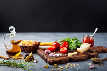 Italian food background with vine tomatoes, basil, spaghetti, olives, parmesan, olive oil, garlic Ingredients on stone table. Copy space.