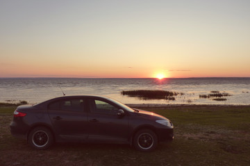 car on the shore at sunset background.