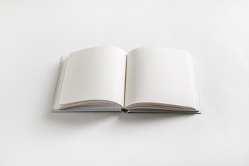 Opened blank book on white paper background.