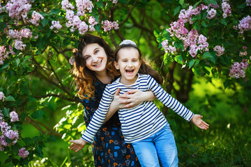 Mother and daughter having fun together. Happy cheerful family. Mom and cute little girl on a background of a bush of blossoming lilacs. Selective focus.
