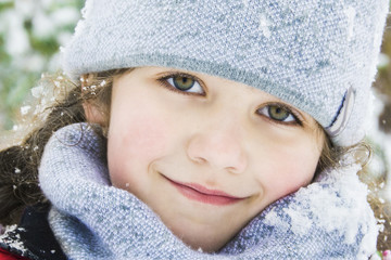 In winter, in the forest, there is a beautiful little girl in a hat and scarf. Close-up.