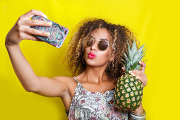 Beautiful Girl selfie with a smartphone. Beautiful young African American woman with afro hairstyle and sunglasses