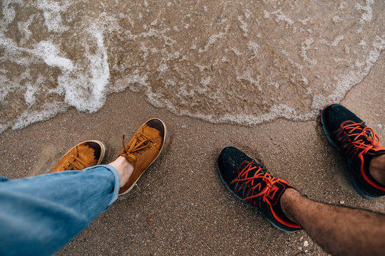 feet on the sand near the water