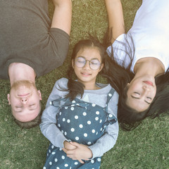 Young family with daughter laying in the park on the green grass and looking at the camera, top view.