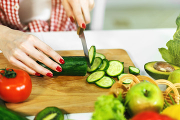 Caucasian girl with neat red manicure cutting cucumber on chopping board, wearing checked red shirt and white t-shirt, sitting at the table full of green and healthy food, closeup