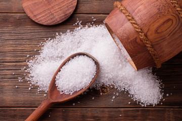 Sea salt in a keg on a wooden background