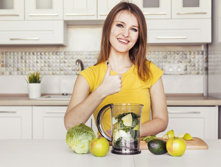 Beautiful girl wears yellow t-shirt preparing green smoothie at the kitchen table, concept of healthy lifestyle, peaceful morning time